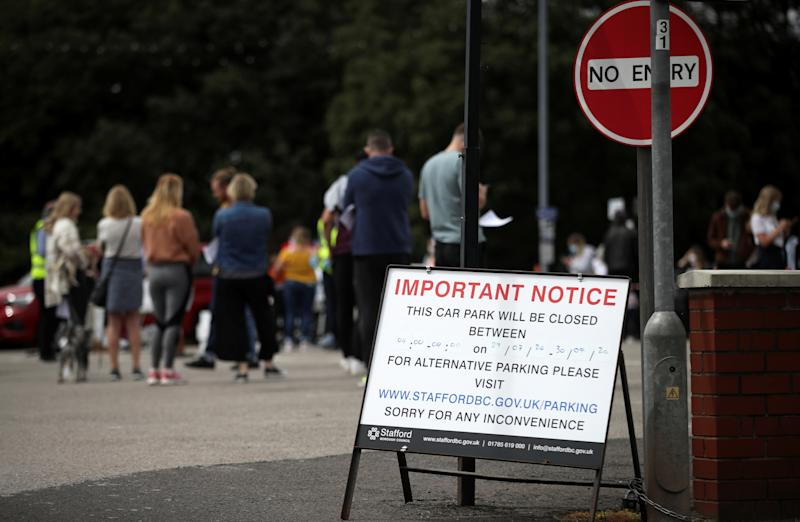 People queue near the Crown and Anchor pub following a spike in cases of the coronavirus disease (COVID-19) to visitors of the pub in Stone, Britain, July 29, 2020. REUTERS/Carl Recine