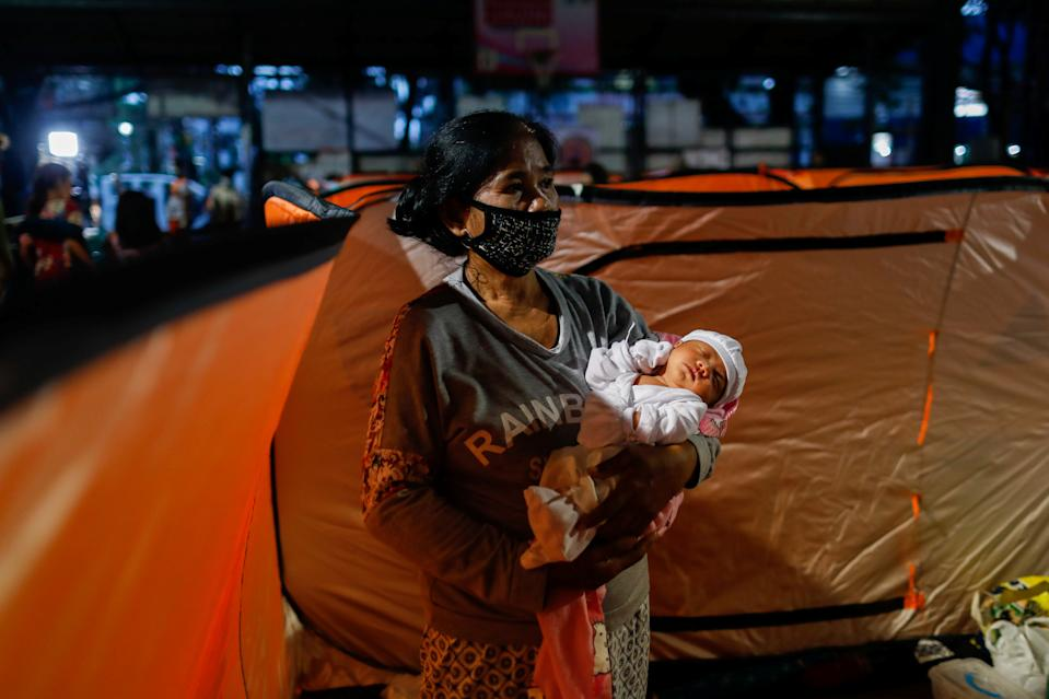 FILE PHOTO: A woman wearing a mask for protection against the coronavirus disease (COVID-19) carries a baby inside a modular tent at an evacuation center, where residents from low-lying areas took shelter following Typhoon Goni, in Quezon City, Metro Manila, Philippines, November 2, 2020. REUTERS/Eloisa Lopez