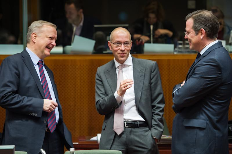 EU Commissioner for Economic and Monetary Affairs Olli Rehn, left, smiles as he talks with Swedish Finance Minister Anders Borg, right, and Executive Board member of the European Central Bank Jorg Asmussen at the start of an Ecofin meeting at the European Council building in Brussels, Tuesday Dec. 10, 2013. (AP Photo/Geert Vanden Wijngaert)