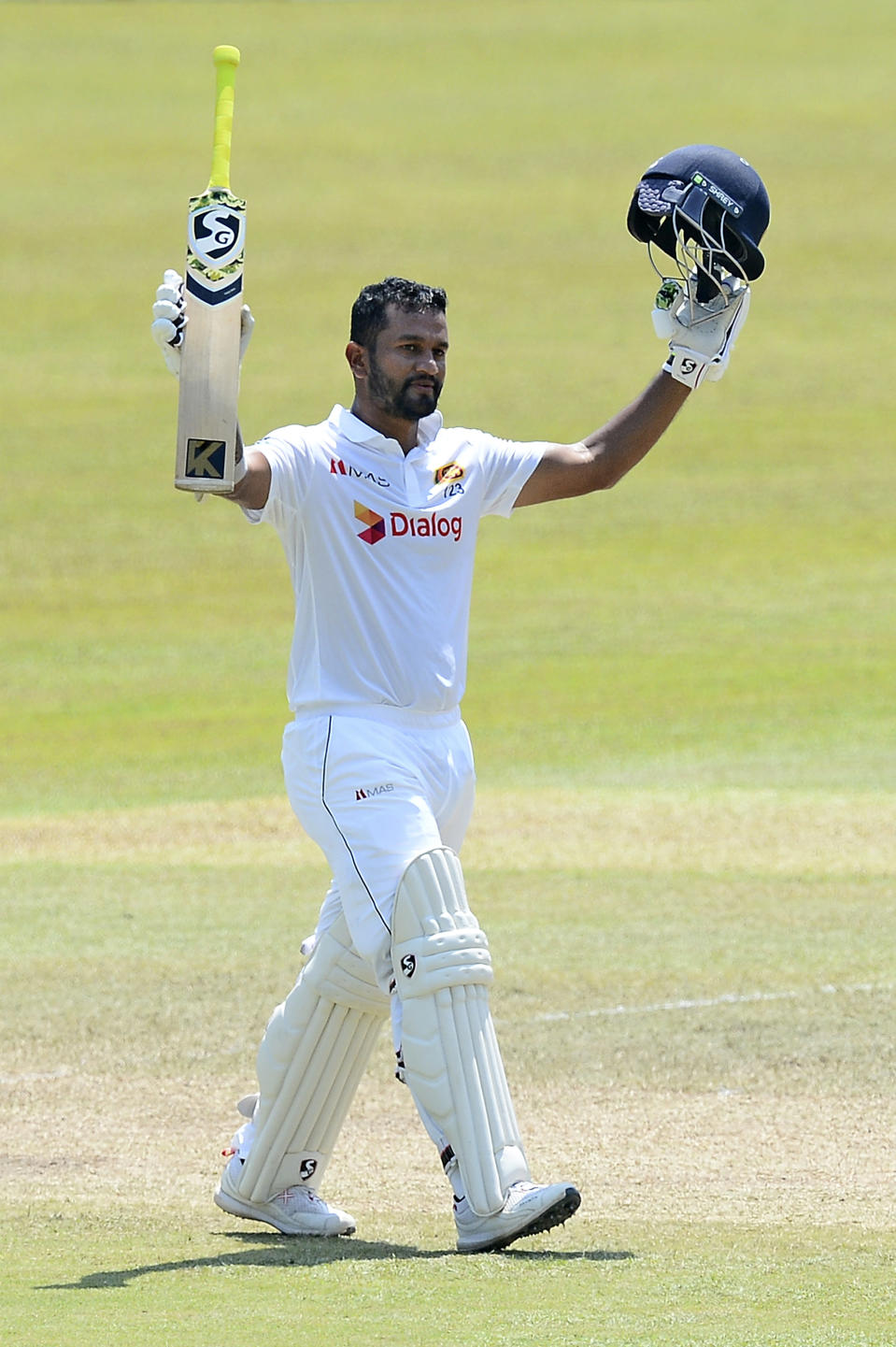 Sri Lankan captain Dimuth Karunaratne raises his bat as he celebrates scoring a century during the fourth day of the first test cricket match between Sri Lanka and Bangladesh in Pallekele, Sri Lanka, Saturday, April 24, 2021.( AP Photo/Sameera Peiris)