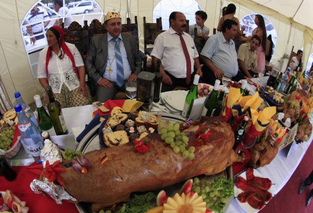 Self proclaimed international king of gypsies Dan Stanescu (2nd L) sits among relatives at a table with a roasted pig on display during the traditional ethnic Roma festival in Costesti, 210 km (128 miles) west of Bucharest, September 8, 2012. Following their tradition, thousands of Roma from all over Romania, which has Europe's largest Roma community, gather every year to celebrate the birthday of St. Mary, to make wedding arrangements for their sons and daughters and to show off their wealth. REUTERS/Radu Sigheti (ROMANIA - Tags: SOCIETY FOOD)