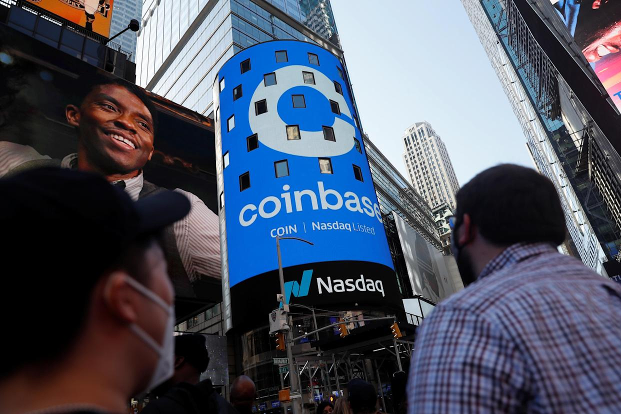 People watch as the logo for Coinbase Global Inc, the biggest U.S. cryptocurrency exchange, is displayed on the Nasdaq MarketSite jumbotron at Times Square in New York, U.S., April 14, 2021. REUTERS/Shannon Stapleton