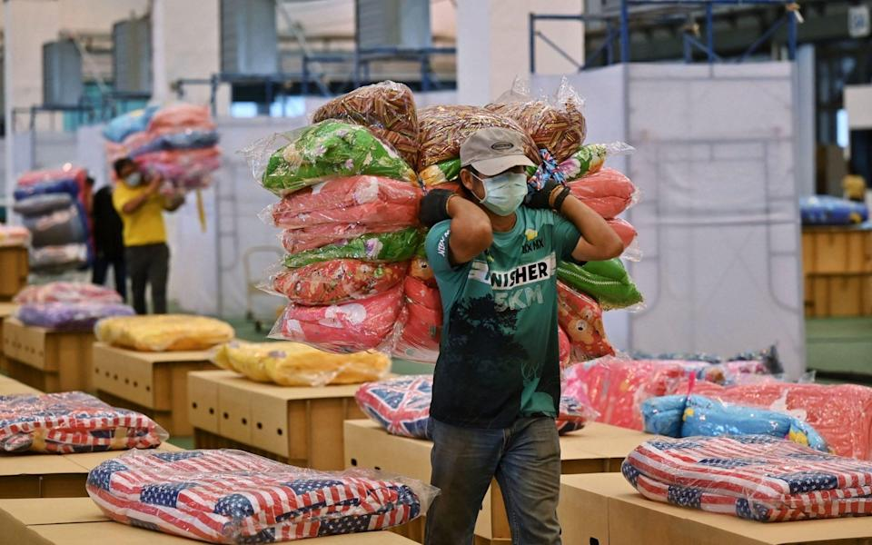 Workers prepare mattresses and blankets for 1,800 cardboard beds at the coronavirus field hospital at Don Mueang International Airport - LILLIAN SUWANRUMPHA/AFP
