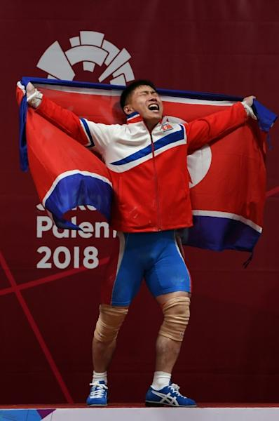 Gold medallist O Kang Chol of North Korea celebrates during the victory ceremony of the men's 69kg weightlifting event during the 2018 Asian Games in Jakarta on August 22, 2018