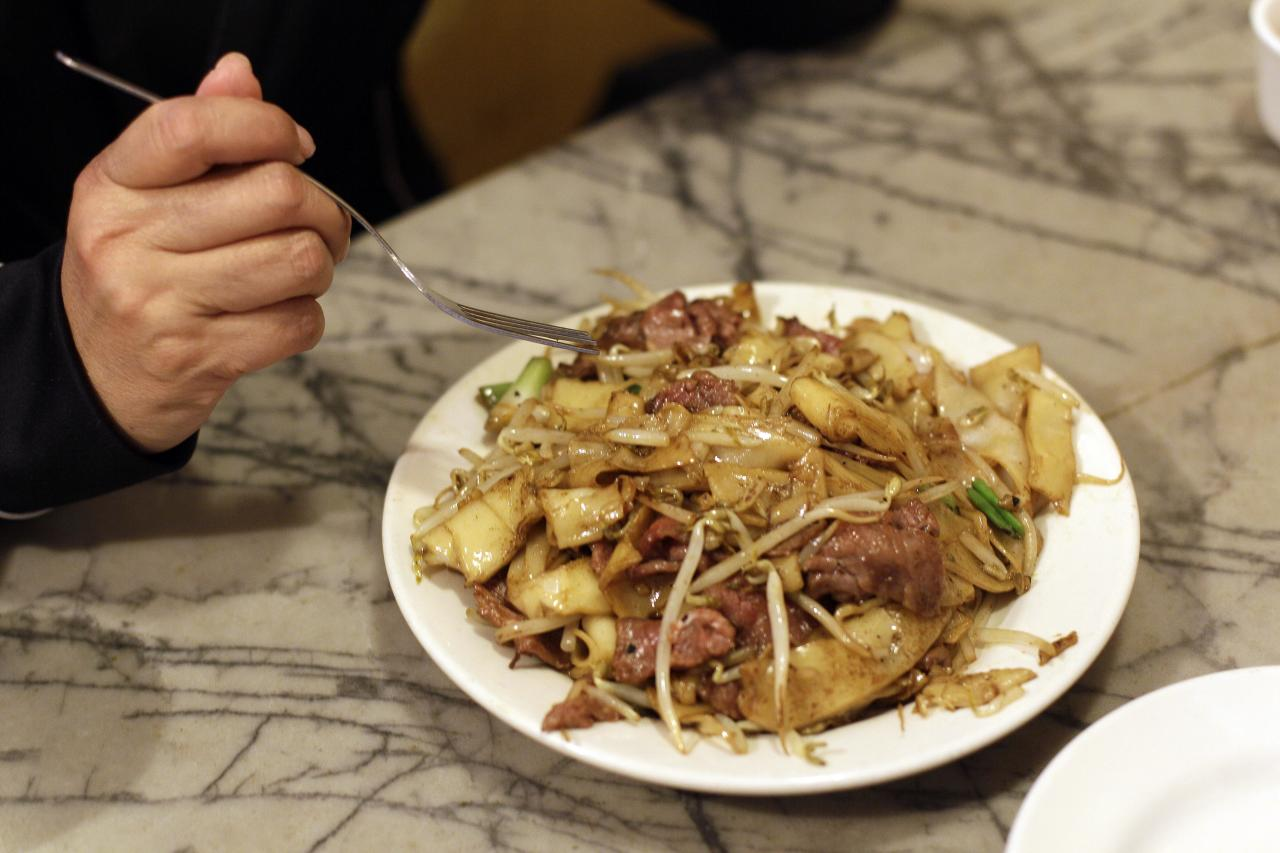 """A woman begins to eat a dish of beef chow fun for lunch at the Sam Wo restaurant in Chinatown in San Francisco, Friday, April 20, 2012. The 100-year-old Chinese restaurant known for having """"the world's rudest waiter"""" is shutting its doors and serving its last customers Friday. (AP Photo/Eric Risberg)"""