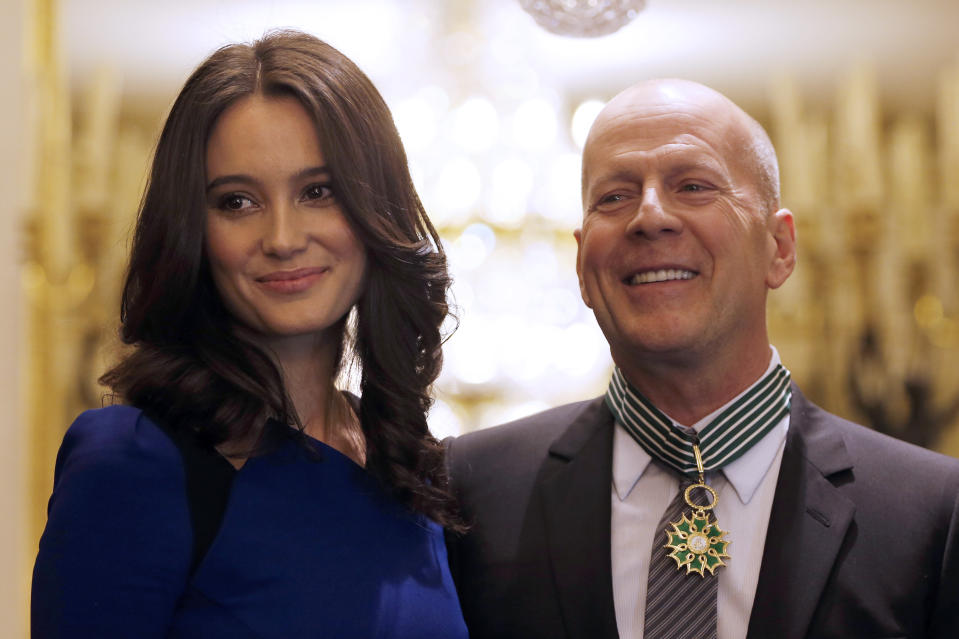 Actor Bruce Willis of the U.S. (R) poses with his wife Emma Heming (L) after being awarded as Commandeur des Arts et lettres (Commander in the Order of Arts and Letters) by French Culture minister Aurelie Filippetti during a ceremony at the ministry in Paris , February 11, 2013. REUTERS/Charles Platiau (FRANCE - Tags: ENTERTAINMENT POLITICS)