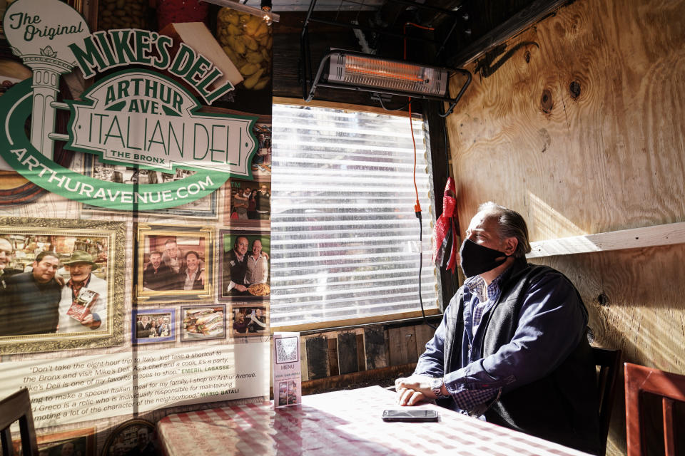 David Greco of Mike's Deli, an Italian delicatessen within the Arthur Avenue Retail Market situated in the historically Italian immigrant neighborhood of the Bronx borough, sits in his company's outdoor dining space, Wednesday, March 3, 2021, in New York. (AP Photo/John Minchillo)