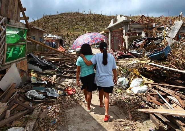 Typhoon Haiyan survivors walk amid ruins of buildings in Maraboth, Philippines, Thursday, Nov. 14, 2013. The Canadian Forces are considering sending a detachment of three to six Griffon helicopters to help with relief efforts in the Philippines in the wake of typhoon Haiyan. THE CANADIAN PRESS/AP/Dita Alangkar