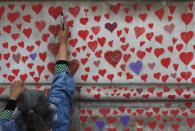 People paint red hearts onto the COVID-19 Memorial Wall mourning those who have died, opposite the Houses of Parliament on the Embankment in London, Monday, April 5, 2021. Hearts are being painted onto the wall in memory of the many thousands of people who have died in the UK from coronavirus. (AP Photo/Frank Augstein)