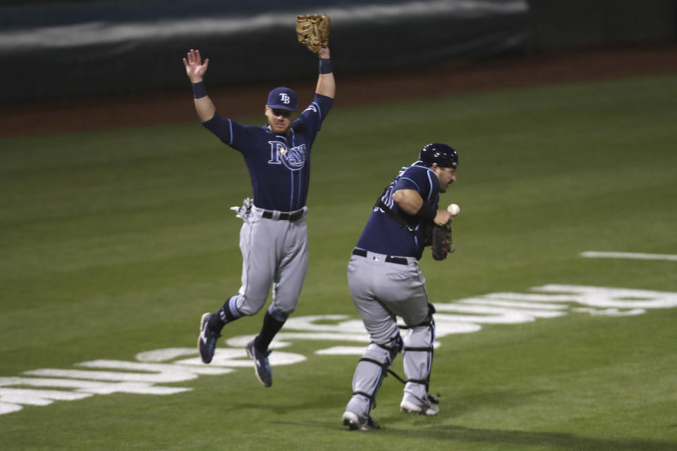 Tampa Bay Rays' Mike Zunino, right, misses a foul ball hit by Oakland Athletics' Tony Kemp as Mike Brosseau avoids the play during the seventh inning of a baseball game in Oakland, Calif., Friday, May 7, 2021. (AP Photo/Jed Jacobsohn)
