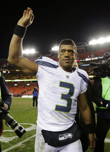 Seattle Seahawks quarterback Russell Wilson waves as he leaves the field after an NFL wild card playoff football game against the Washington Redskins in Landover, Md., Sunday, Jan. 6, 2013. The Seahawks defeated the Redskins 24-14. (AP Photo/Matt Slocum)
