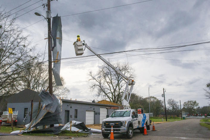A utility worker looks to repair lines with the roof of Kelley Electric draped on the lines after downtown Moundville was hit by severe weather, Wednesday, March 17, 2021, in Moundville, Ala. Possible tornadoes knocked down trees, toppled power lines and damaged homes in rural Chilton County and the Alabama communities of Burnsville and Moundville, where power was out and trees blocked a main highway. (AP Photo/Vasha Hunt)