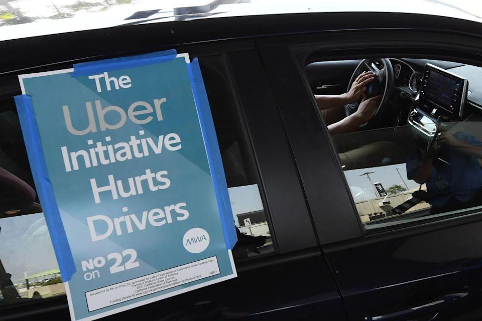 A ride share driver participates in a protest by drivers and their supporters, August 20, 2020 at Los Angeles International Airport in Los Angeles, California. - Rideshare service rivals Uber and Lyft were given a temporary reprieve on August 20 from having to reclassify drivers as employees in their home state of California by August 21. (Photo by Robyn Beck / AFP) (Photo by ROBYN BECK/AFP via Getty Images)