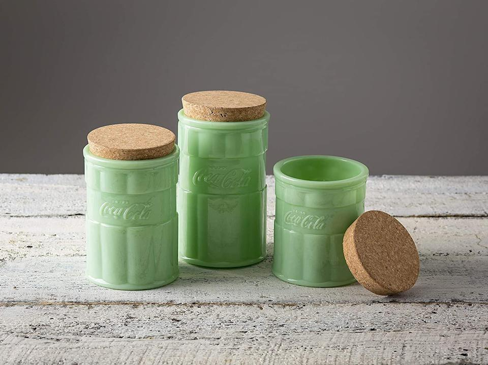 """<p>This Coca-Cola collection doubles down on the nostalgia by using retro milk-green glass. These canisters are great for keeping anything from coffee grounds to sugar safe and sound.</p> <p><strong>Buy It: $23.99 each; <a href=""""https://www.amazon.com/TableCrafts-Coca-Cola-Jadeite-Medium-Canister/dp/B07PC8KJ63/ref=as_li_ss_tl?ie=UTF8&linkCode=ll1&tag=slhomejadeitekitchentrendkyarborough0820-20&linkId=b6f68f59b1deb546453ce5f97761b4df&language=en_US"""" rel=""""nofollow noopener"""" target=""""_blank"""" data-ylk=""""slk:amazon.com"""" class=""""link rapid-noclick-resp"""">amazon.com</a></strong></p>"""