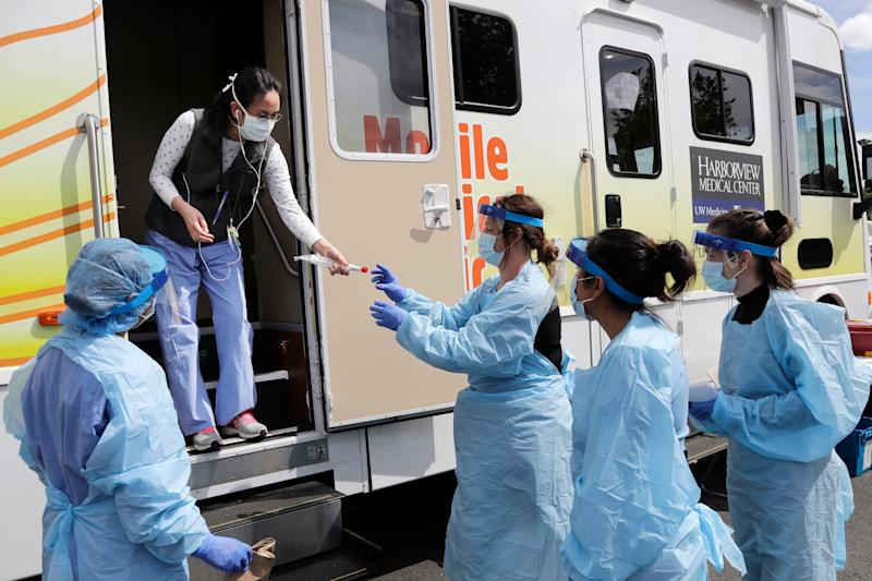 Medical assistants wait to be handed testing kits at a drive-up coronavirus testing site in Seattle.