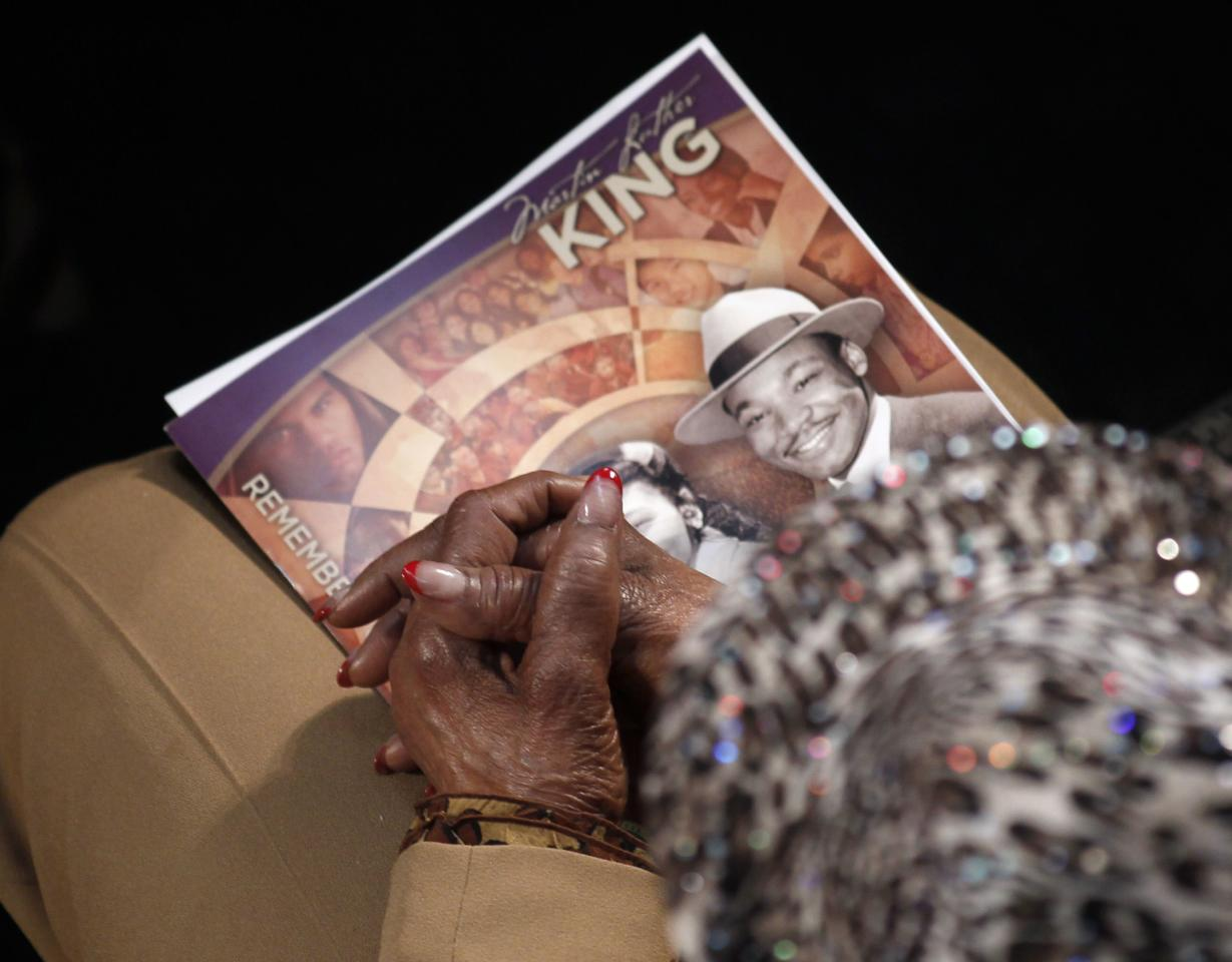 A visitor holds a commemorative booklet as she listens during the Martin Luther King, Jr. 46th Annual Commemorative Service at Ebenezer Baptist Church in Atlanta, Georgia January 20, 2014. REUTERS/Tami Chappell (UNITED STATES - Tags: POLITICS ANNIVERSARY)