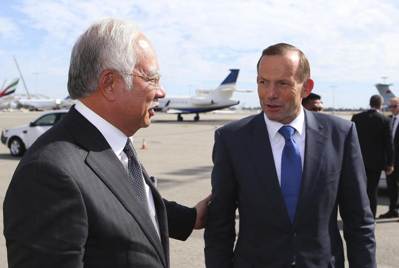 FILE - In this April 3, 2014 file photo, Australian Prime Minister Tony Abbott, right, chats with his Malaysian counterpart Najib Razak at Perth International Airport as Razak prepares to depart Australia after his visit during the search of the missing Malaysia Airlines flight MH370, in Perth, Australia. The leaders of Malaysia and Australia have used warm and glowing terms to assure the world that their partnership in the desperate hunt for the missing airliner is built on a firm and abiding friendship. But it's also an odd-couple relationship that has proved brittle in the past and has been blighted by hostility, rivalries and cultural misunderstandings. (AP Photo/Paul Kane, File)