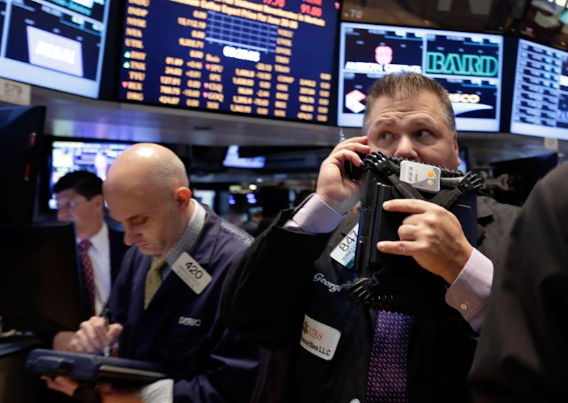 Trader Geroge Ettinger, right, works on the floor of the New York Stock Exchange, Thursday, June 20, 2013. Financial markets are sliding after the Federal Reserve said it could end its huge bond-buying program by the middle of next year. (AP Photo/Richard Drew)