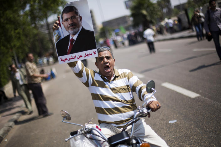 "An Egyptian man holds a poster supporting Egypt's Islamist President Mohammed Morsi, with Arabic writing that reads ""no alternative to legitimacy, during a rally near Cairo University in Giza, Egypt, Tuesday, July 2, 2013. With a military deadline for intervention ticking down, protesters seeking the ouster of Egypt's Islamist president sought Tuesday to push the embattled leader further toward the edge with another massive display of people power.(AP Photo/Manu Brabo)"