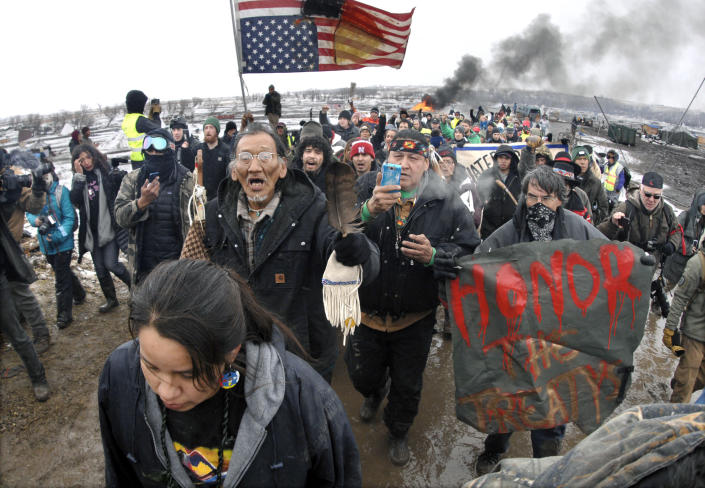 FILE - In this Feb. 22, 2017, file photo, a large crowd representing a majority of the remaining Dakota Access Pipeline protesters march out of the Oceti Sakowin camp near Cannon Ball, N.D. After President Joe Biden revoked Keystone XL's presidential permit and shut down construction of the long-disputed pipeline that was to carry oil from Canada to Texas, opponents of other pipelines hoped the projects they've been fighting would be next. (Mike McCleary/The Bismarck Tribune via AP)