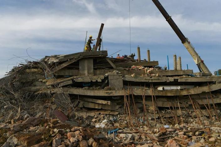 Rescue personnel used excavators, drills and power saws to clear concrete (AFP Photo/TANG CHHIN Sothy)