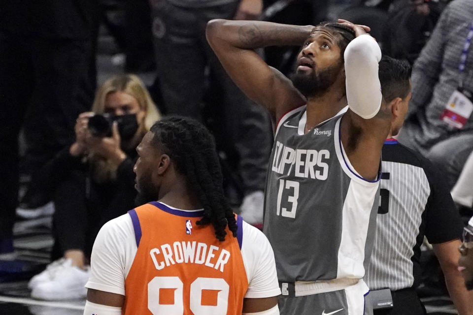 Los Angeles Clippers guard Paul George, right, reacts after being charged with a foul as Phoenix Suns forward Jae Crowder stands by during the second half in Game 4 of the NBA basketball Western Conference Finals Saturday, June 26, 2021, in Los Angeles. (AP Photo/Mark J. Terrill)