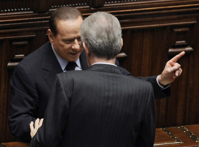 """FILE - In this  Friday, Nov. 18, 2011 file photo, Italy's former Premier Silvio Berlusconi, left, talks to Italian Premier Mario Monti, back to camera, at the lower chamber in Rome. Although Berlusconi resigned in disgrace a year ago, has been convicted of tax fraud and now faces plunging poll numbers, the media baron confirmed to reporters Saturday, Dec. 8, 2012, that he'll try for a fourth term. Berlusconi yanked support for Premier Mario Monti's technocrat government on Thursday, increasing the prospects for early elections. Monti calls the political crisis triggered by the loss of Berlusconi's support """"manageable"""" and says his government has rescued Italy from financial disaster. (AP Photo/Gregorio Borgia, File)"""