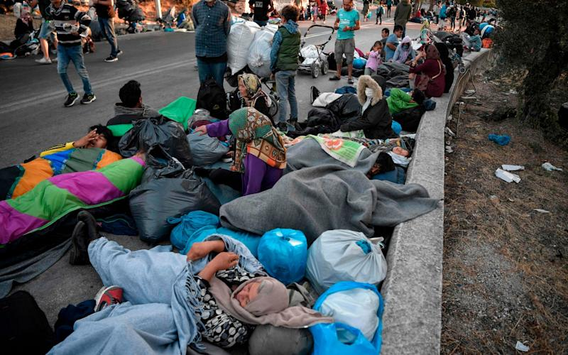 Thousands of asylum seekers are sleeping in roads near the camp - AFP