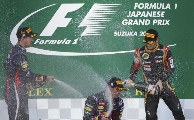Red Bull Formula One driver Sebastian Vettel (L) of Germany celebrates on the podiun with second-placed Red Bull Formula One driver Mark Webber of Australia and third-placed Lotus Formula One driver Romain Grosjean (R) of France after winning the Japanese F1 Grand Prix at the Suzuka circuit October 13, 2013. REUTERS/Toru Hanai (JAPAN - Tags: SPORT MOTORSPORT F1)