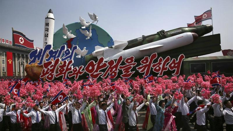 North Korean men and women wave flags and plastic flowers as a float with model missiles and rockets with words that read