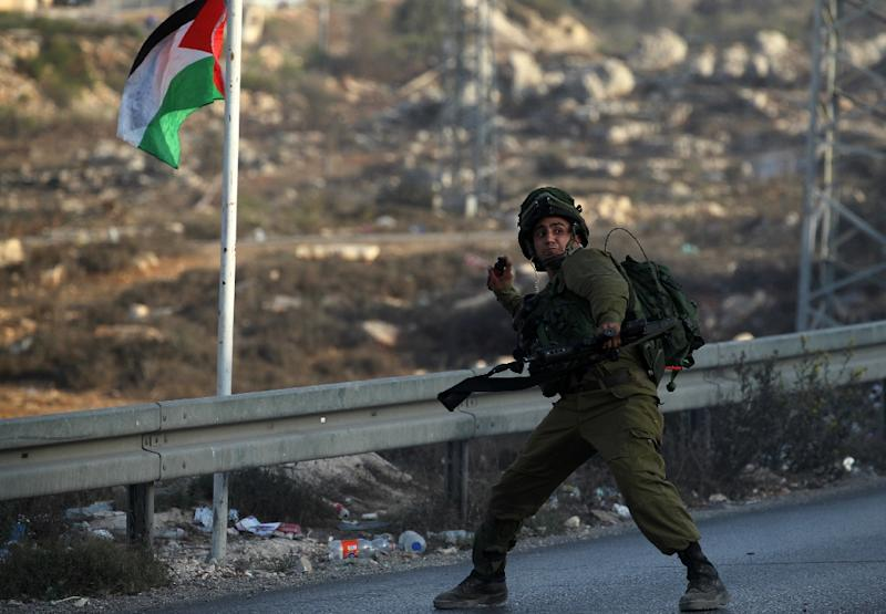 An Israeli soldier hurls a smoke grenade during clashes with Palestinian youth close to the Jewish settlement of Bet El, in the West Bank city of Ramallah on October 4, 2015 (AFP Photo/Abbas Momani)