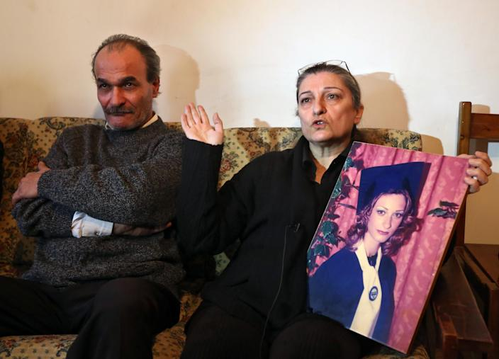 In this Tuesday, Feb. 18, 2014 photo, George Abu Chacra and his wife Josephine speak as she holds a picture of their daughter Christelle, who they say was poisoned by their son-in-law and died shortly afterward in hospital, during an interview with The Associated Press at their home in Beirut, Lebanon. Although Lebanon appears very progressive on women rights compared to other countries in the Middle East, domestic violence remains an unspoken problem and the nation's parliament has yet to vote on a bill protecting women's rights nearly three years after it was approved by the Cabinet. On Saturday, March, 8, 2014, about 5,000 people marched in Beirut to demand protection for women and urged the parliament to vote on the domestic violence law. (AP Photo/Bilal Hussein)