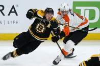 Boston Bruins center Brad Marchand (63) and Philadelphia Flyers defenseman Travis Sanheim (6) skate for position during the third period of an NHL hockey game Thursday, Jan. 21, 2021, in Boston. (AP Photo/Elise Amendola)