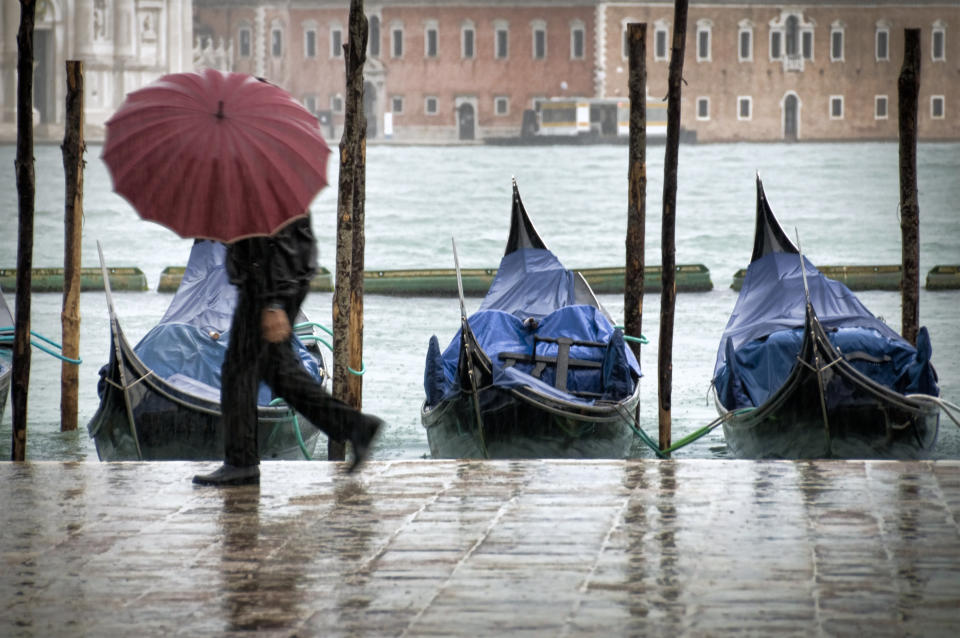 Unidentifiable pedestrian with umbrella walking along St.Mark waterfront in Venice(Italy) during a rainy winter day.