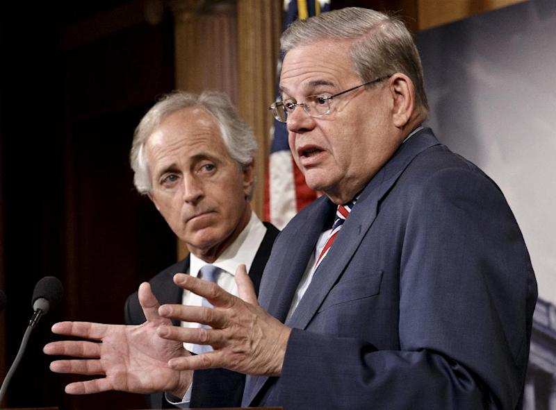 Senate Foreign Relations Committee Chairman Sen. Robert Menendez, D-N.J., accompanied by the committee's ranking member, Sen. Bob Corker, R-Tenn., gestures during a news conference on Capitol Hill in Washington, Thursday, March 27, 2014, just after the Senate passed the Ukraine Aid Bill in a show of support for the people of Ukraine and a get-tough message for Russian President Vladimir Putin for taking over the Crimea region. (AP Photo/J. Scott Applewhite)