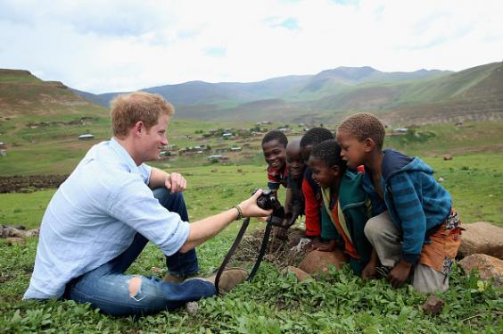 Prince Harry shows children a photograph he has taken on a visit to Lesotho (Chris Jackson/Getty Images)