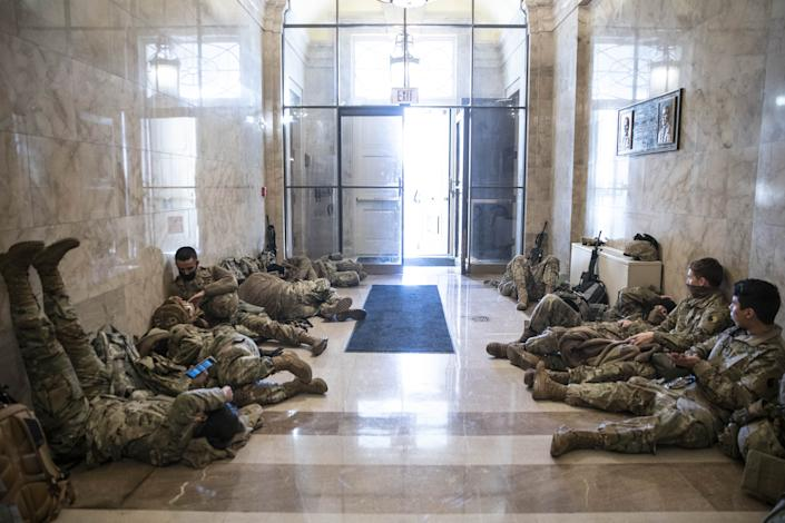 Members of the National Guard rest in a hallway of the Capitol