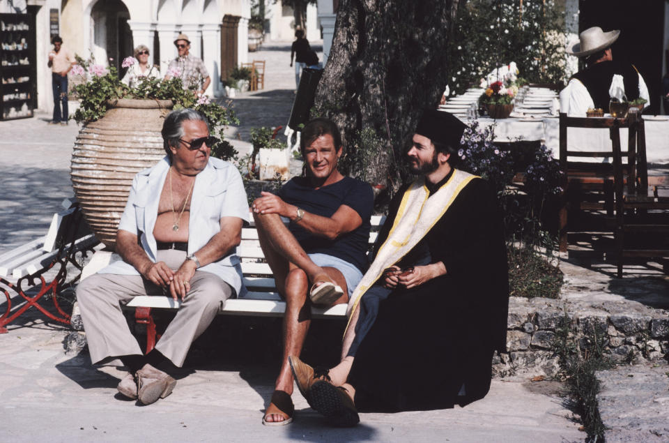 From left to right, producer Albert R. Broccoli (1909 - 1996), English actor Roger Moore and producer and screenwriter Michael G. Wilson on the set of the James Bond film 'For Your Eyes Only', 1981. Wilson is in costume for his customary bit-part, this time as a Greek Orthodox priest. (Photo by Keith Hamshere/Getty Images)