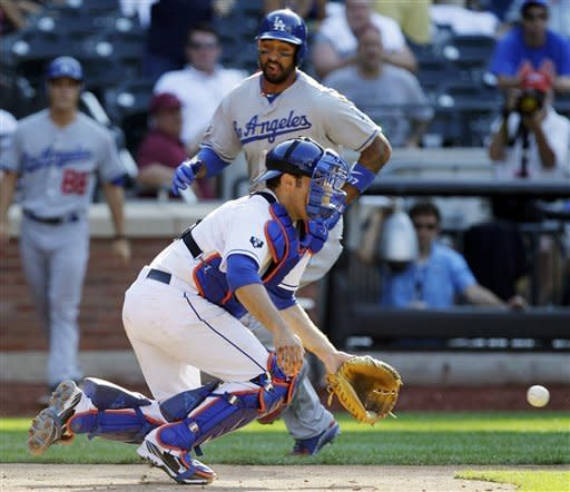 Los Angeles Dodgers' Matt Kemp scores ahead of the throw to New York Mets catcher Mike Nickeas on Matt Treanor's 12th-inning, two-run single in their baseball game at Citi Field in New York, Sunday, July 22, 2012. The Dodgers won 8-3 in the 12th inning. (AP Photo/Kathy Willens)