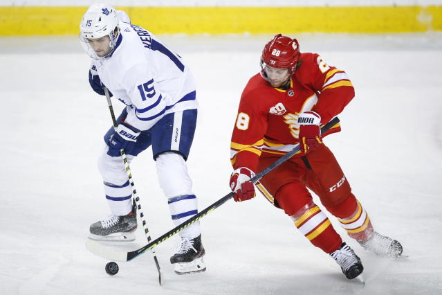 Toronto Maple Leafs' Alexander Kerfoot, left, has the puck stolen from him by Calgary Flames' Elias Lindholm during the first period of an NHL hockey game, Thursday, Dec. 12, 2019 in Calgary, Alberta. (Jeff McIntosh/The Canadian Press via AP)