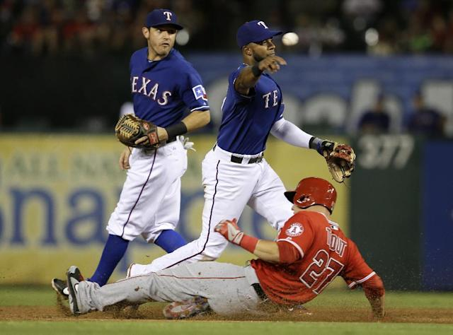 Texas Rangers shortstop Elvis Andrus, makes the throw to first for the double play after getting the force at second on Los Angeles Angels' Mike Trout (27) in the third inning of a baseball game, Friday, Sept. 27, 2013, in Arlington, Texas. Rangers second baseman Ian Kinsler, rear, watches the play develop where the Angels Josh Hamilton was out at first. (AP Photo/Tony Gutierrez)