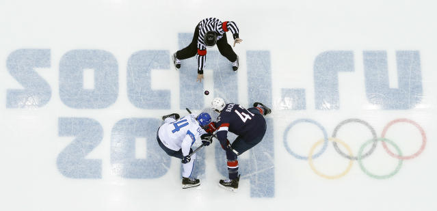 Finland forward Mikael Grandlund and USA forward David Backes face off to start the men's bronze medal ice hockey game at the 2014 Winter Olympics, Saturday, Feb. 22, 2014, in Sochi, Russia. (AP Photo/David J. Phillip )
