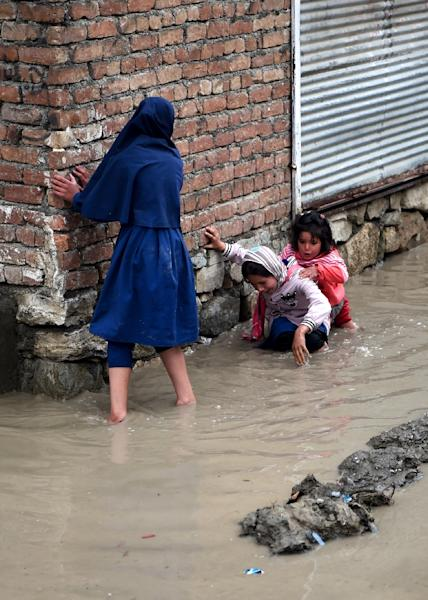 Afghan girls try to make their way home throught flooded streets in the Afghan capital, Kabul (AFP Photo/WAKIL KOHSAR)