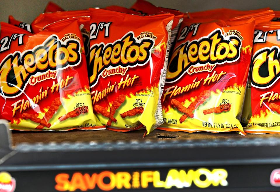 Bags of Flamin' Hot Cheetos lined up on a convenience store shelf
