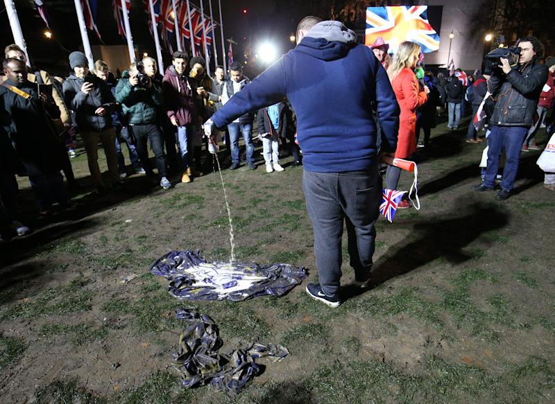 A pro-Brexit supporter pours beer onto an EU flag in Parliament Square, London, ahead of the UK leaving the European Union at 11pm on Friday.