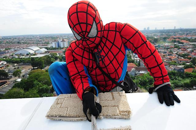 SURABAYA, INDONESIA - JULY 12: Indonesian 'Spider-Man' window cleaner, 37-year-old Teguh prepares to clean the glass windows of the 18-storey Alana Hotel on July 12, 2013 in Surabaya, Indonesia. Teguh is a specialist glass window cleaner working on high-rise buildings wearing a Spider-Man uniform and working at an altitude of over 500 meters above ground level. He earns between Rp. 5 million and 15 million depending on the height of the building and the level of difficulty. (Photo by Robertus Pudyanto/Getty Images)