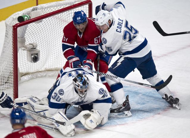 Tampa Bay Lightning defenseman Matt Carle tries to take out Montreal Canadiens' Max Pacioretty from behind goaltender Ben Bishop during the first period of an NHL hockey game Tuesday, Nov. 12, 2013, in Montreal. (AP Photo/The Canadian Press, Paul Chiasson)
