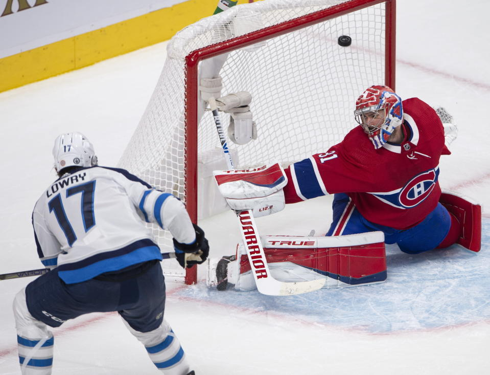Winnipeg Jets' Adam Lowry (17) scores a goal against Montreal Canadiens goaltender Carey Price (31) during the second period of an NHL Stanley Cup playoff hockey game in Montreal, Sunday, June 6, 2021. (Ryan Remiorz/The Canadian Press via AP)