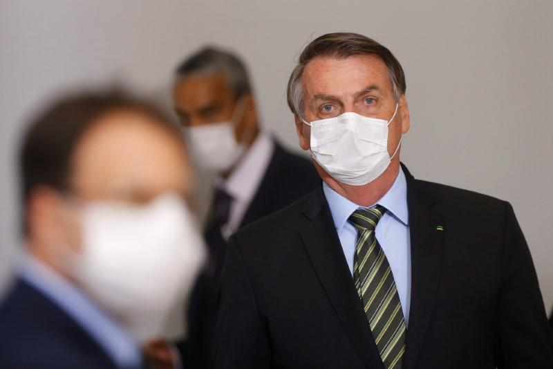 Brazil's President Jair Bolsonaro wearing a protective face mask arrives to a press conference to announce federal judiciary measures to curb the spread of the coronavirus disease (COVID-19) in Brasilia