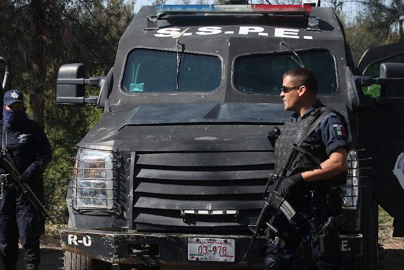 State police stand guard at a ranch along the Jalisco-Michoacan highway in Tanhuato, Michoacan State, on May 23, 2015, after federal police killed 42 New Generation suspects in what authorities described as an intense gunfight